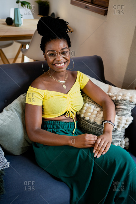 Positive young African American female in bright yellow shirt and transparent eyeglasses looking at camera with bright friendly toothy smile while relaxing on couch in bright studio apartment
