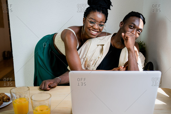 Cheerful African American female in crop top hugging positive husband working at laptop remotely in bright cozy studio apartment