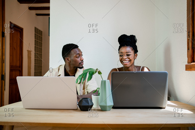 Front view of positive young African American man and woman in casual clothes and smiling while working together on laptops at home