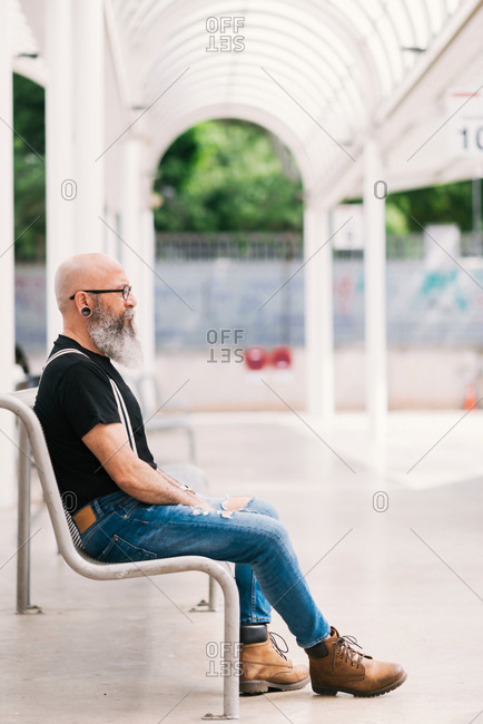 Side view of brutal aged male with earring and beard sitting on bench in park and looking away