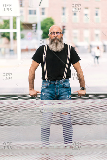 Brutal aged male with earring and beard sitting on bench in park and looking at camera