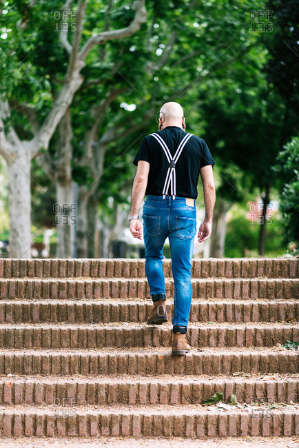 Back view of anonymous bald male in stylish outfit walking up stone steps during city stroll in summer