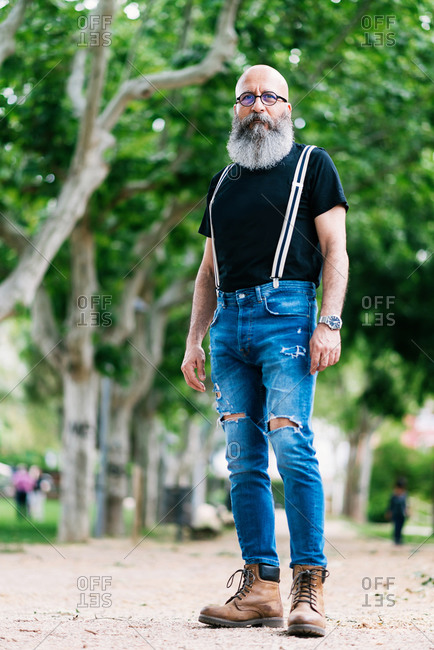 Low angle of determined aged bearded male wearing stylish clothes standing on street in park and looking at camera