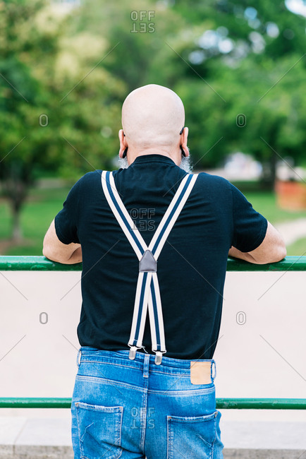Back view senior male with bald head and long gray beard leaning on fence in park and confidently looking away