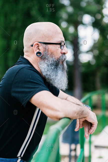 Calm senior male with bald head and long gray beard leaning on fence in park and confidently looking away