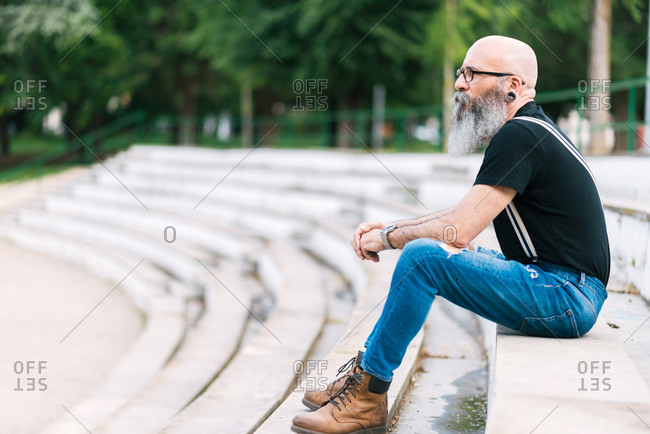 Side view of senior confident bearded male sitting on stone stairs in urban park and looking away