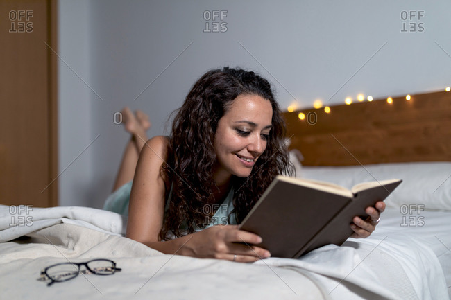 Pensive female lying on comfortable bed and reading interesting story in book while spending weekend at home