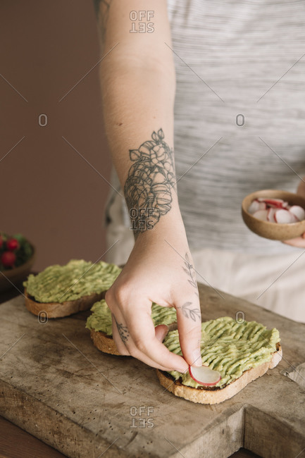 Young woman garnishing guacamole on baked bread while standing in kitchen at home