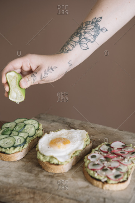 Woman squeezing lime on bread garnished with vegetable and guacamole on serving dish at kitchen