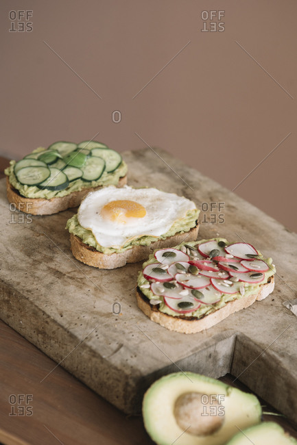 Bread garnished with fresh vegetable and guacamole on serving dish at kitchen