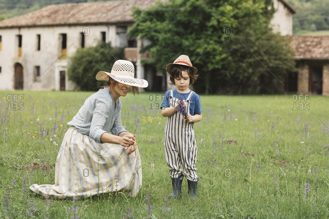 Mother and son collecting flowers while standing in meadow