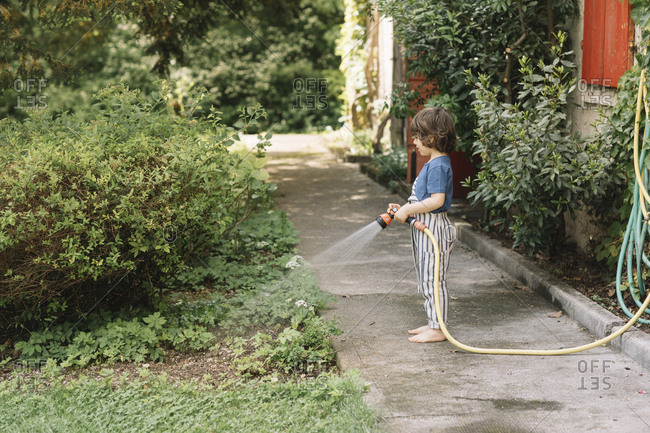 Boy watering plants while standing on footpath at back yard