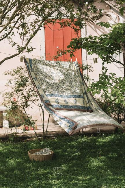 Bed sheet hanging on clothesline at backyard