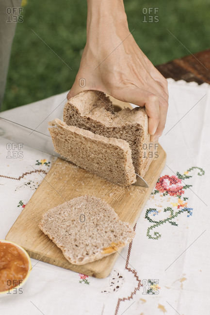 Female hand cutting bread on cutting board in garden
