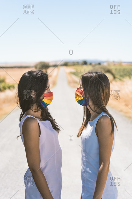 Women with rainbow face mask looking at each other while standing on road