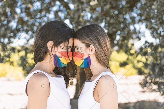 Young women with rainbow standing face to face against tree