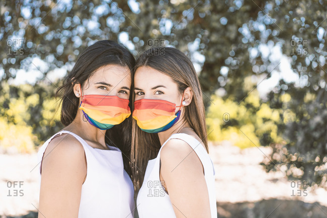 Young women with multi colored face mask standing against tree