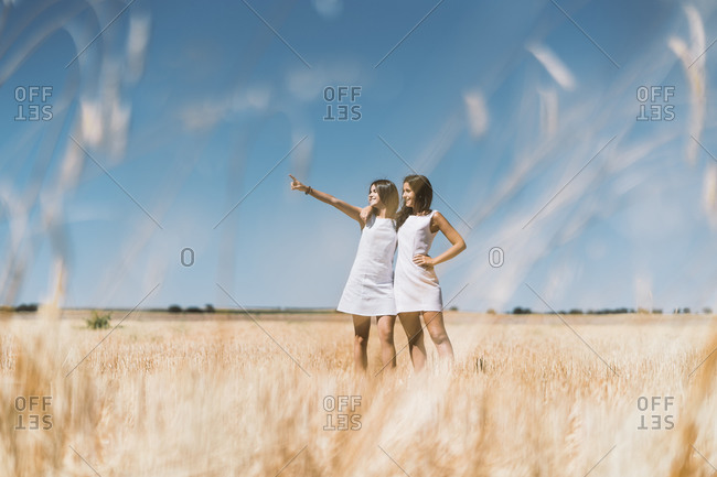 Young women pointing while standing on agricultural field