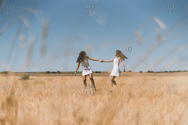 Lesbian couple holding hands while playing in agricultural field