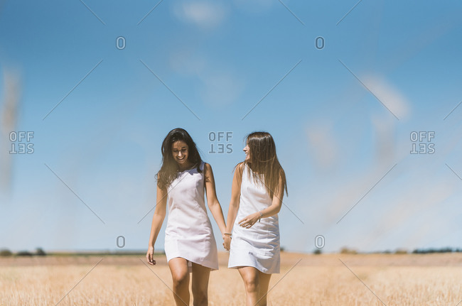 Beautiful lesbian couple talking while walking on agricultural field against clear sky