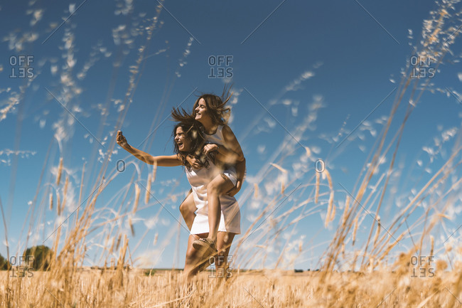 Woman taking selfie while piggybacking on agricultural field