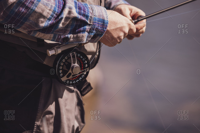 Close-up of fisherman tying fishing rod on waist