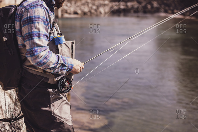 Fly fisherman catching fish from river on sunny day
