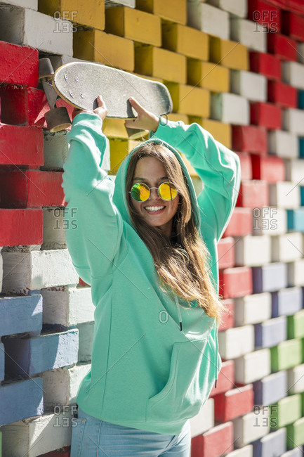 Woman with hand raised holding skateboard while standing against colored wall