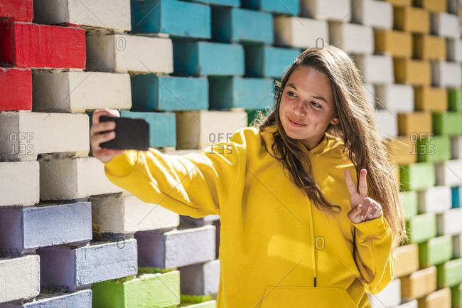 Young woman taking selfie on smart while standing by colored brick wall