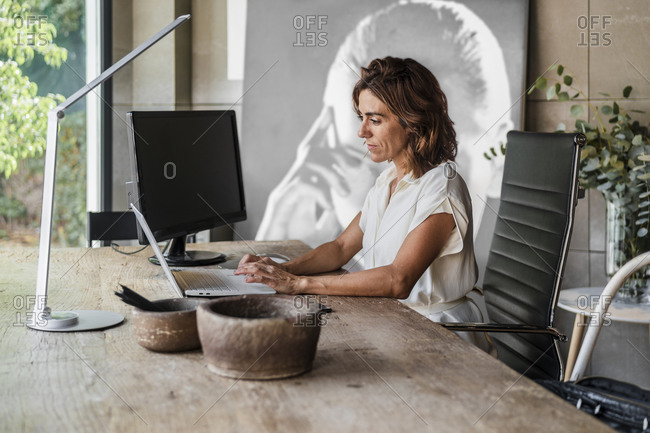 Businesswoman working on laptop while sitting in office