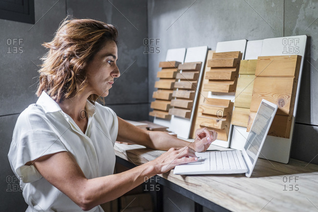 Woman working on laptop with wood tiles on desk at office