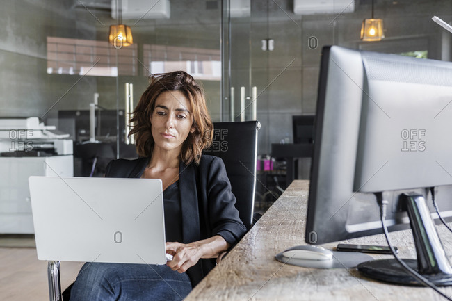 Businesswoman working on laptop while sitting on chair at office