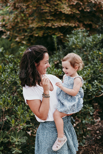 Smiling mother picking up daughter while standing in public park