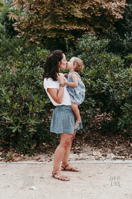 Mother and daughter kissing each other while standing in public park