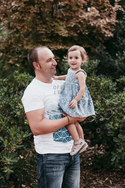 Father picking up daughter while standing in public park