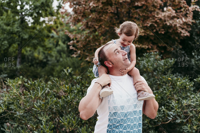 Father carrying daughter on shoulder while standing in park