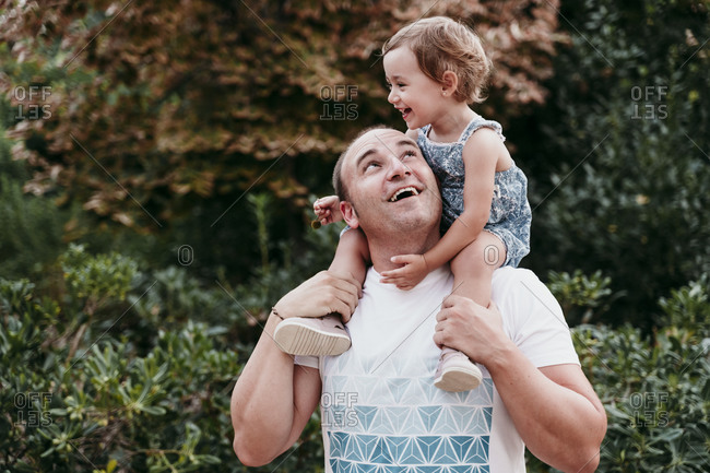 Happy father carrying daughter on shoulder while standing in park