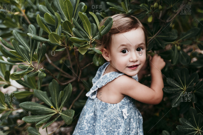 Cute little girl standing in public park against green leaves