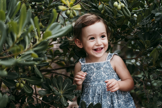 Happy little girl standing in public park against green leaves