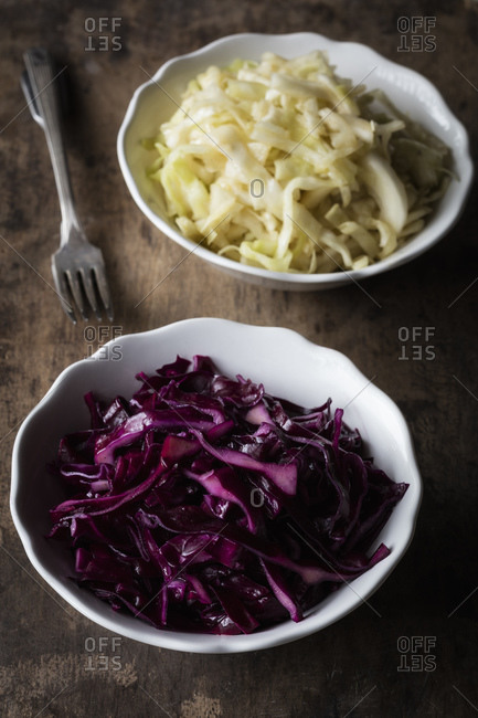 Chopped red and white cabbage bowl on table