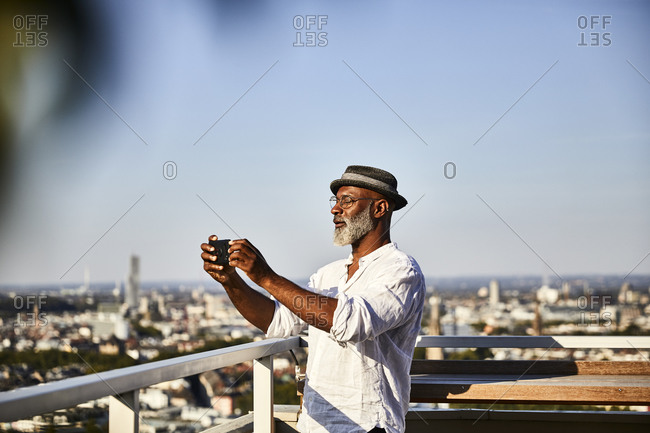 Mature man taking selfie while using smart phone standing on building terrace