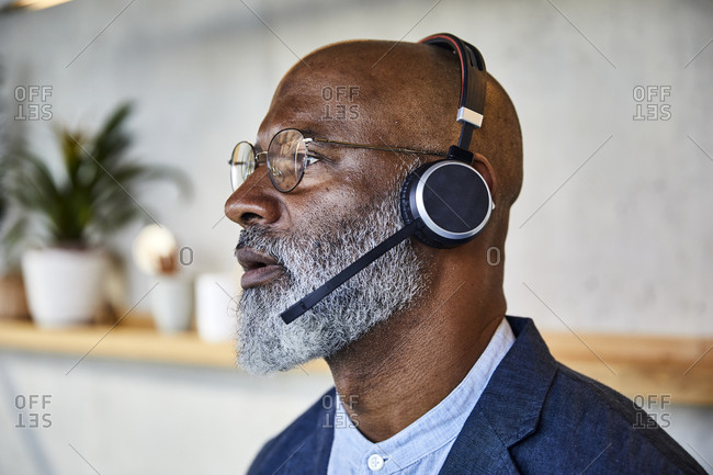 Close-up of man with headphone looking away while standing at home