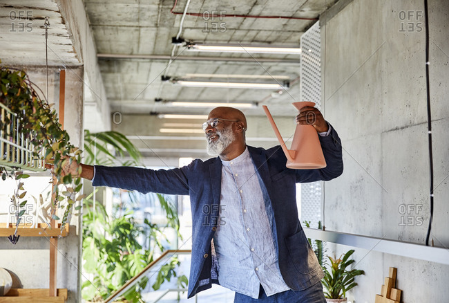 Mature man holding watering can looking at plant while standing at home