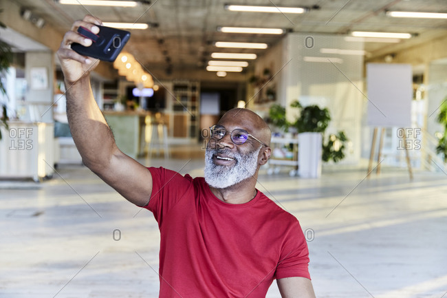 Happy mature man in red t-shirt taking selfie while sitting at rooftop