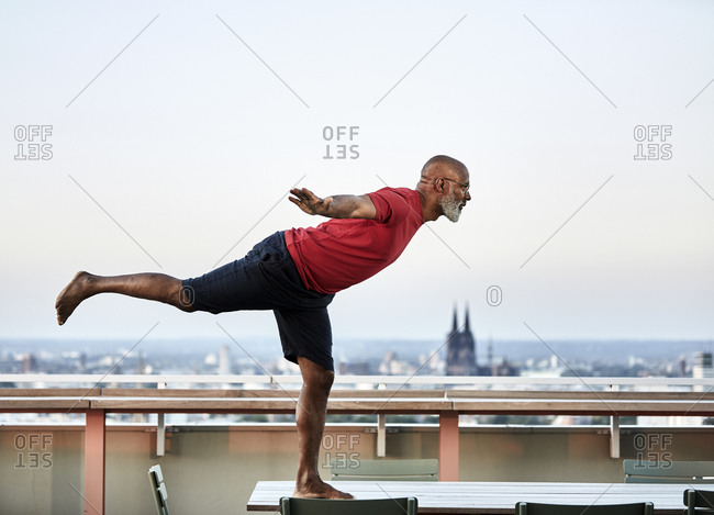 Bald man balancing on dining table while practicing yoga at building terrace during sunset