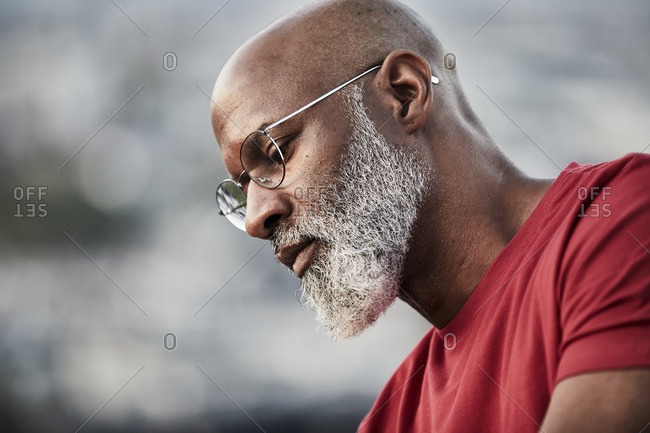 Thoughtful bald man with white beard looking down at building terrace during sunset