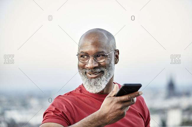 Smiling bald man talking through smart phone while looking away at building terrace during sunset