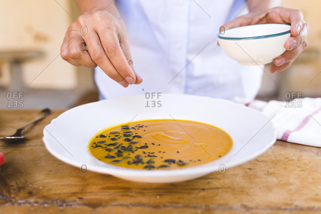 Woman putting sesame seed in soup while standing at table