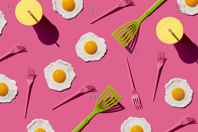 Studio shot of plastic forks- kitchen spatulas- disposable cups and fried eggs