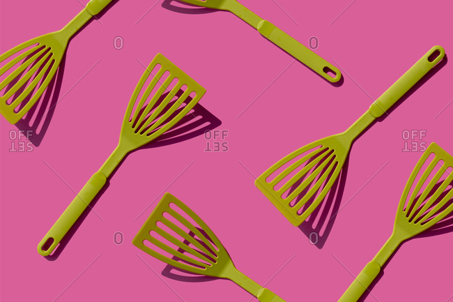 Pattern of green spatulas against pink background